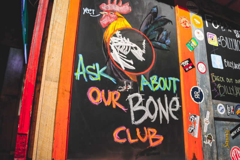 """a chalkboard in billy jacks reads """"ask about our bone club"""" and features a drawing of a chicken"""